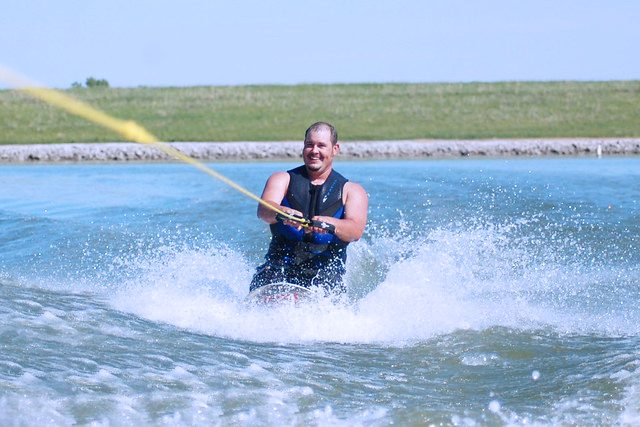 man smiling while kneeboarding in the lake